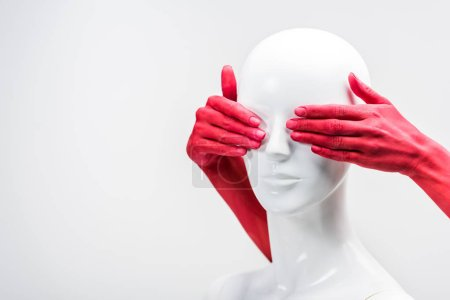 Photo for Cropped image of woman in red paint covering mannequin eyes isolated on white - Royalty Free Image
