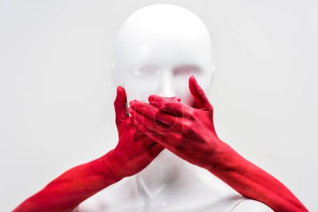 cropped image of woman in red paint covering mannequin mouth with hands isolated on white