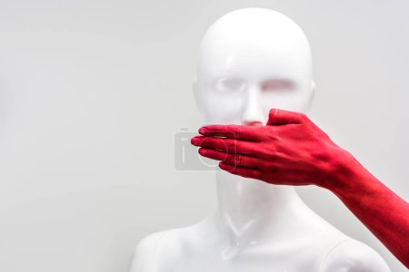 cropped image of girl in red paint covering mannequin mouth with hand isolated on white