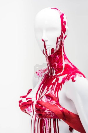 cropped image of girl in red paint touching mannequin breasts isolated on white