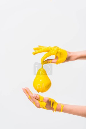 cropped image of woman in yellow paint holding pear isolated on white