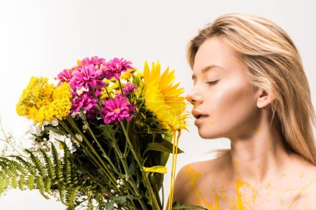 side view of attractive woman with yellow paint on body sniffing flowers isolated on white