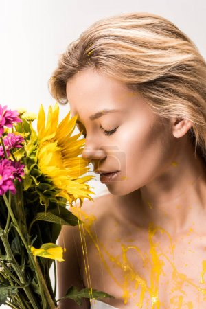 attractive woman with yellow paint on body sniffing bouquet of flowers isolated on white