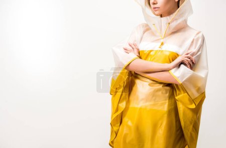 cropped image of woman in raincoat standing with crossed arms isolated on white
