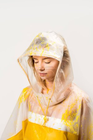 beautiful woman in raincoat and hood painted with yellow paint standing with closed eyes isolated on white