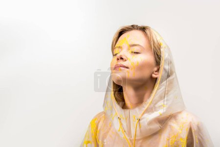 beautiful woman in raincoat painted with yellow paint standing with closed eyes isolated on white