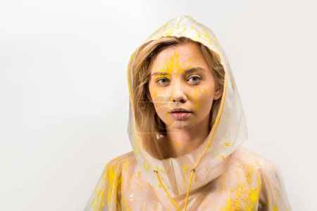 beautiful woman in raincoat painted with yellow paint looking at camera isolated on white
