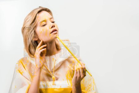 beautiful woman in raincoat painting face with yellow paint isolated on white