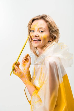 smiling beautiful woman in raincoat painting face with yellow paint isolated on white