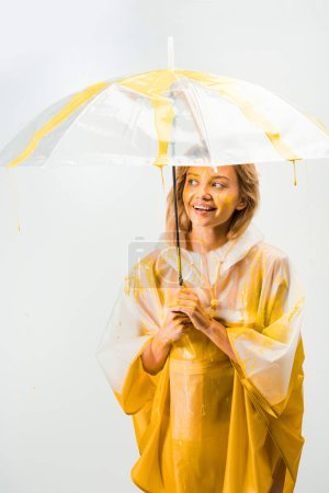 Photo for Happy woman in raincoat painted with yellow paint standing under umbrella isolated on white - Royalty Free Image