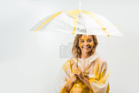smiling attractive woman in raincoat painted with yellow paint standing under umbrella isolated on white