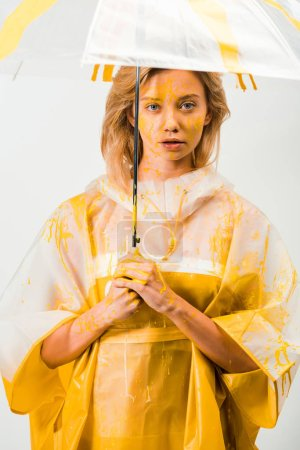 attractive woman in raincoat painted with yellow paint standing under umbrella isolated on white
