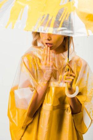 Photo pour Jolie femme en gabardine peint avec une peinture jaune permanent sous égide et toucher les lèvres isolés sur blanc - image libre de droit