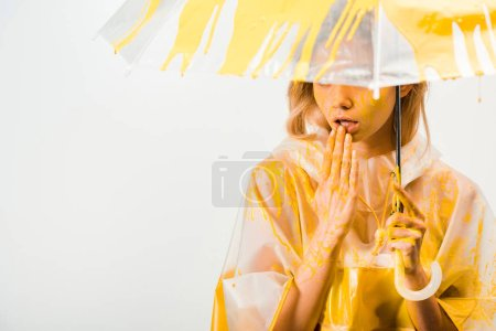 beautiful woman in raincoat painted with yellow paint standing under umbrella and touching lips isolated on white