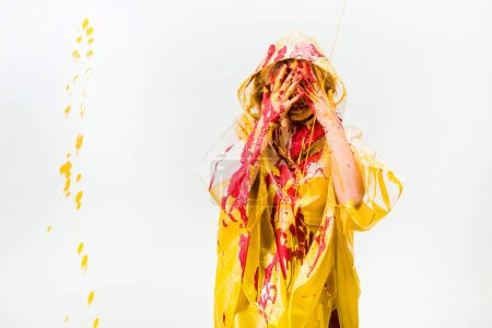 woman in raincoat painted with yellow and red paints protecting face from paints isolated on white