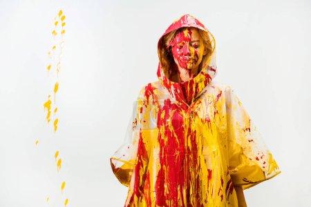 Photo pour Jolie femme en gabardine peint avec de la peinture jaune et rouge, debout les yeux fermés isolé sur blanc - image libre de droit