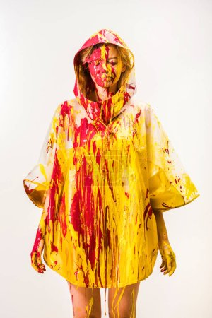 beautiful woman in raincoat painted with yellow and red paints standing with closed eyes isolated on white