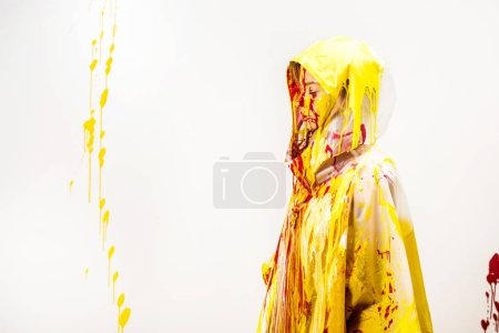 side view of woman in raincoat painted with yellow and red paints standing in hood isolated on white