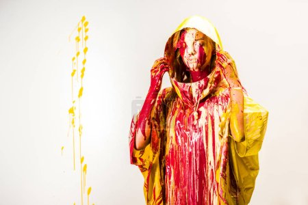 beautiful woman in raincoat painted with yellow and red paints wearing hood isolated on white
