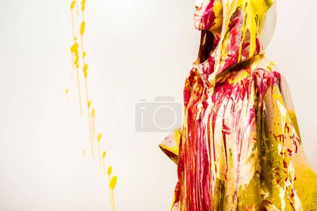 cropped image of woman in raincoat painted with colored paints isolated on white