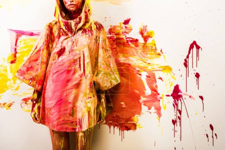 cropped image of woman standing in raincoat painted with yellow and red paints near wall