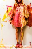 cropped image of woman standing in raincoat painted with yellow and red paints