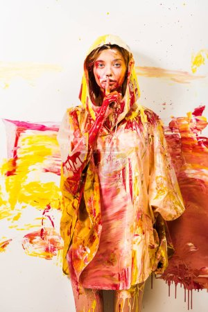beautiful woman in raincoat painted with yellow and red paints showing silence gesture