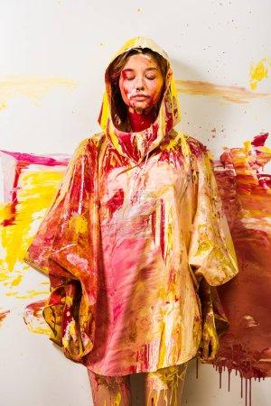 Photo pour Belle femme en gabardine peint avec de la peinture jaune et rouge, debout, yeux fermés - image libre de droit