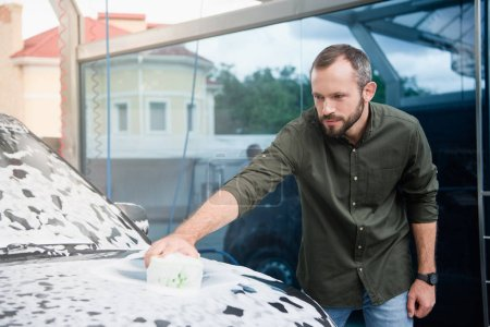 handsome man cleaning car at car wash with rag and foam