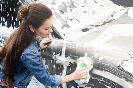 side view of attractive woman cleaning car at car wash with rag and foam