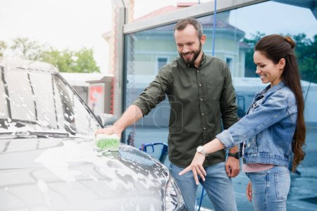 girlfriend pointing on car to boyfriend while he cleaning it at car wash
