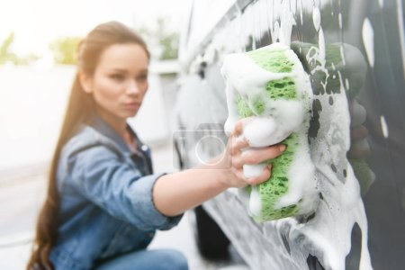 attractive woman cleaning car at car wash with rag and foam