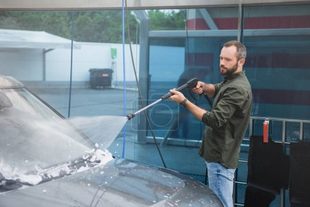 handsome man cleaning car front window at car wash with high pressure water jet
