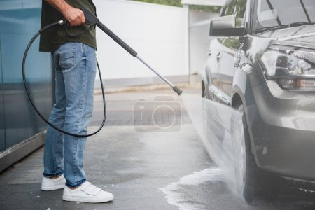 cropped image of man cleaning car at car wash with high pressure water jet