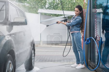 beautiful woman cleaning car at car wash with high pressure water jet