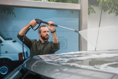 handsome man cleaning car at car wash with high pressure water jet