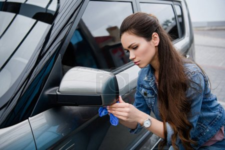 attractive woman cleaning car mirror at car wash with rag