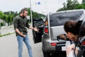 male and female drivers gesturing after car accident on road
