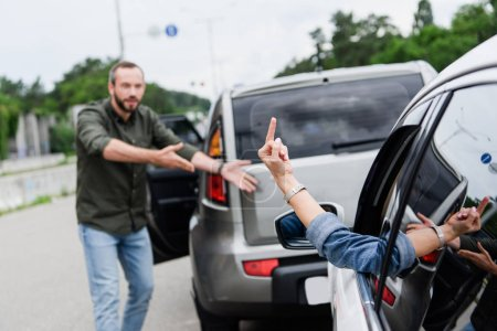 cropped image of driver showing middle finger to man on road