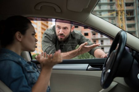angry man gesturing to driver through car window