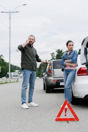 angry and upset drivers standing on road after car accident