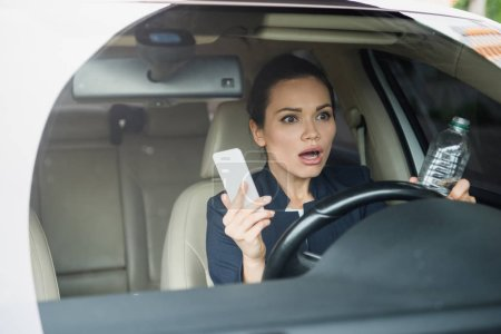 shocked attractive woman holding smartphone and bottle of water while driving car