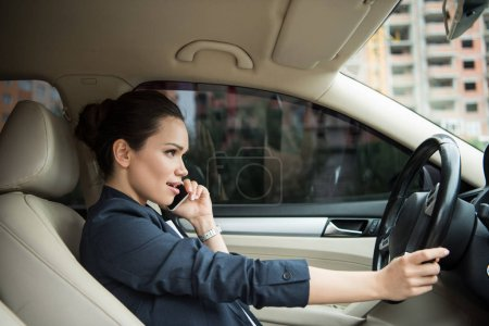 side view of attractive woman using smartphone while driving car