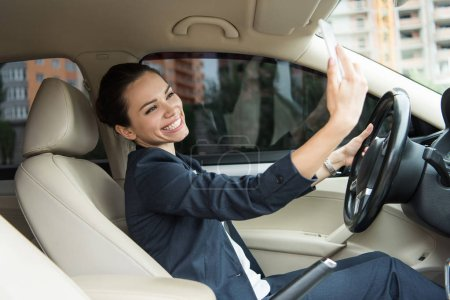 attractive smiling driver taking selfie with smartphone in car