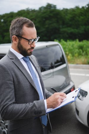 handsome man writing something to car insurance after car accident