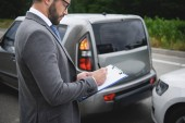side view of  man writing something to car insurance after car accident