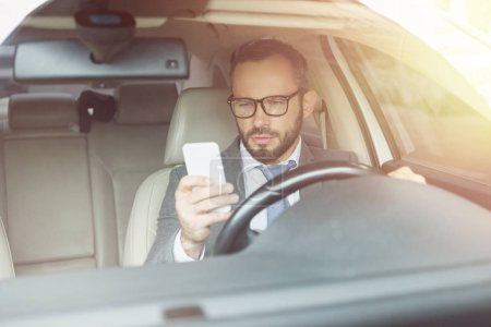 handsome businessman using smartphone while driving car