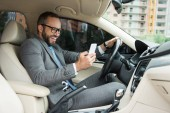 handsome smiling man using smartphone while driving car