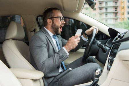 side view of handsome businessman screaming in car and holding smartphone in hand