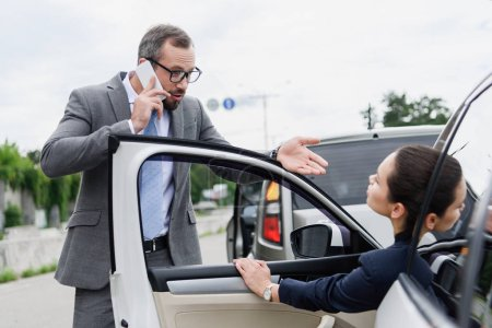 businesspeople quarreling on road after car accident, man talking by smartphone